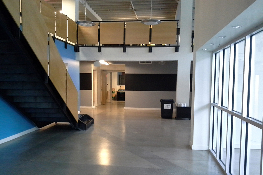 Modern interior of commercial building with wood paneled staircase and railing