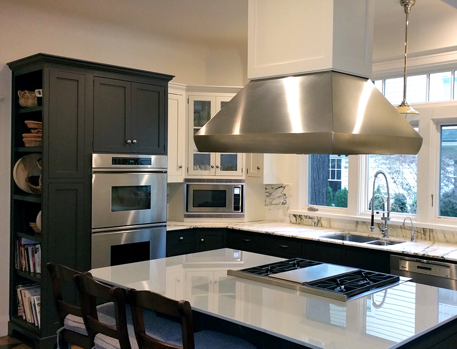 Redesigned kitchen with dark blue and white cabinets with marble countertops