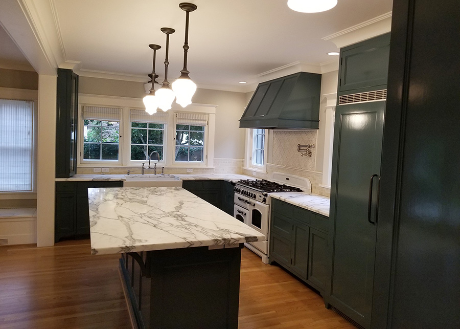 Remodeled kitchen with dark green cabinets and marble countertops