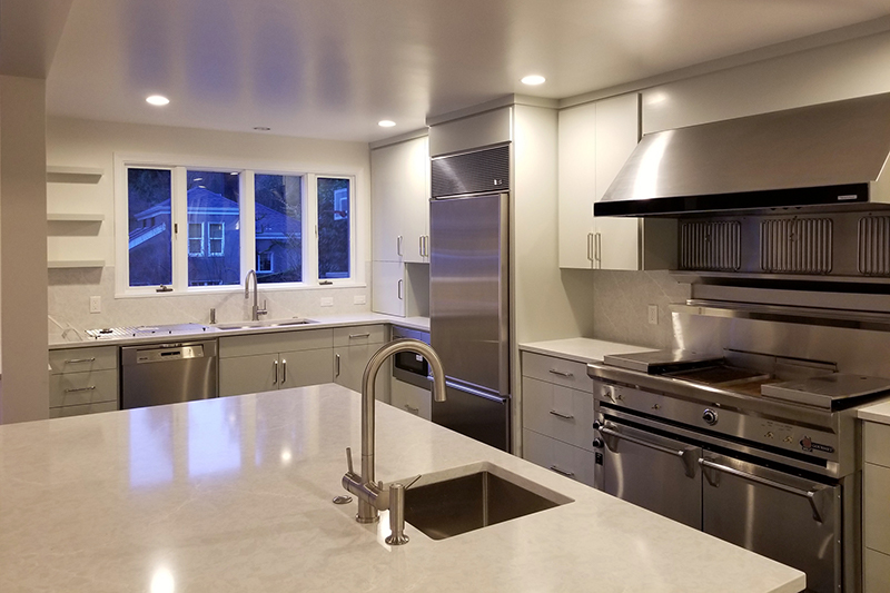 Freshly painted kitchen cabinets with steel appliances
