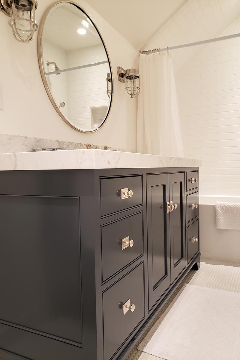 Modern kitchen sink with round mirror and light fixtures