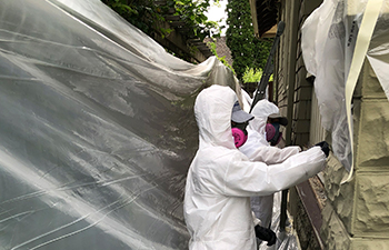 Painters in safety suits removing lead paint