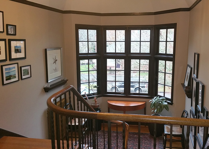 Top of staircase with freshly painted walls and big windows