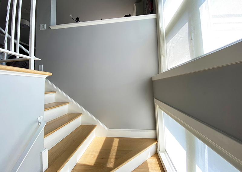 Staircase with grey walls and white trim